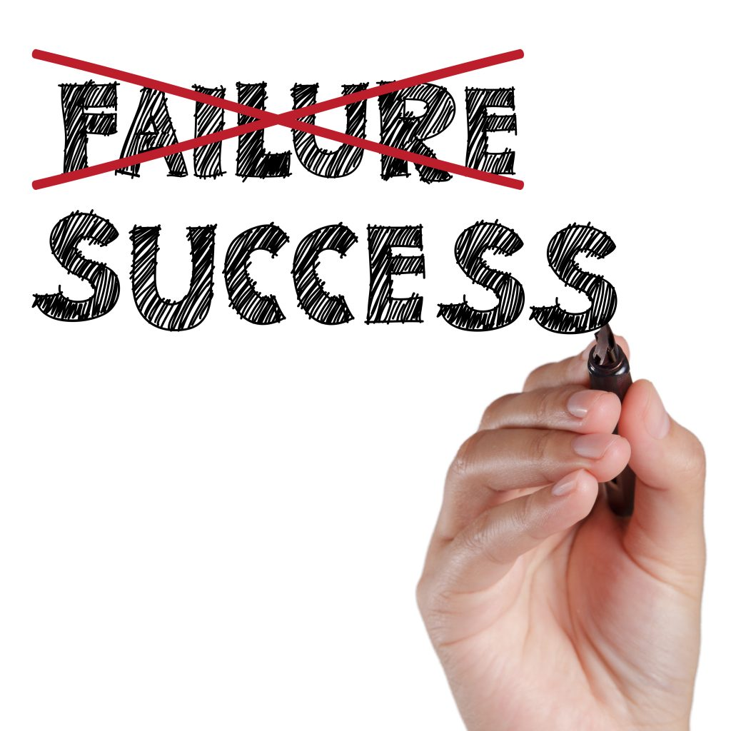 hand crossing out failure and writing success on transparent board.